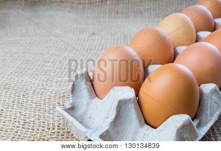 Chicken eggs in box brown eggs on sackcloth background with copy space