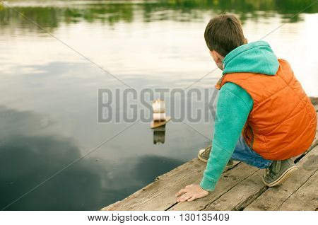 boy launches the toy wooden boat. child playing with a toy sailboat on the river. view from the back. copy space from your text