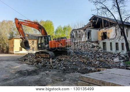 Tyumen, Russia - April 29, 2016: Excavator demolishing barracks for new construction project. Kievskaya street 70