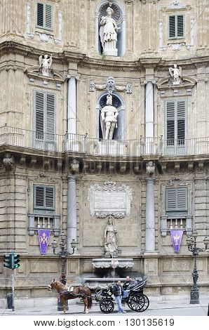 Palermo Italy - April 19 2014: Quattro Canti officially known as Piazza Vigliena is a Baroque square in Palermo Sicily southern Italy. carriage for tourists stops in Piazza dei Quattro Canti waiting for tourists to visit the historic center of the city of