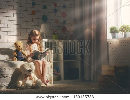 Cute little child girl reading a book. Kid girl sitting in her bed.
