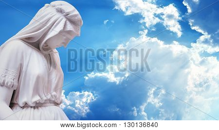 Statue of the mother of Jesus Christ over blue sky background panoramic view