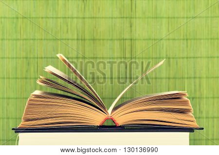The opened book with the turned yellow pages on a green background from bamboo sticks
