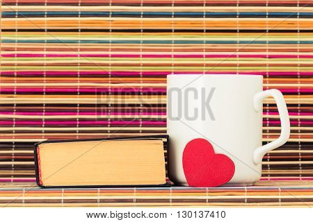 The book near a white cup and red heart before them on a color background from bamboo sticks