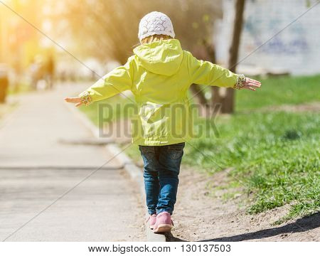 little girl in yellow coat walking in park on curb with hands to sides