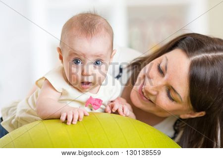 Mother with funny little child doing exercises with gymnastic ball. Concept of caring for the baby's health.