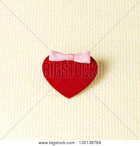 Red female heart with a pink bow on a light mesh background