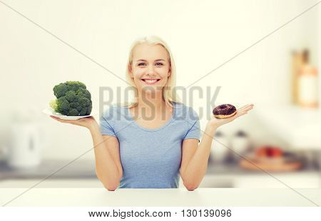 healthy eating, junk food, diet and choice people concept - smiling woman choosing between broccoli and donut over kitchen background