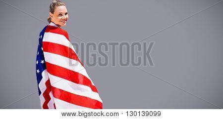 Portrait of happy american sportswoman posing against grey background