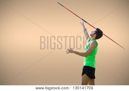 Athletic man throwing a javelin against orange background