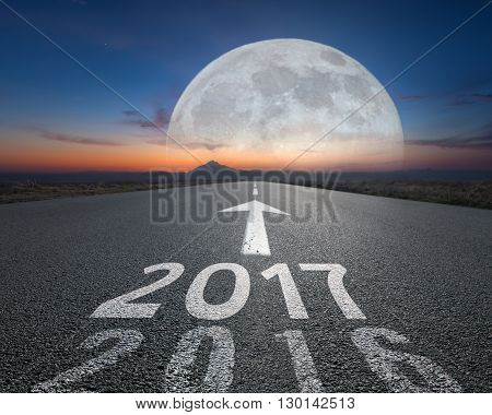 Driving on an empty road towards the big moon to upcoming new 2017 year and living 2016 behind us. Concept for success and passing time.