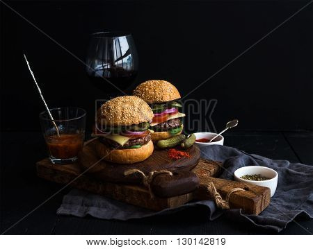 Fresh beef burgers on rustic wooden boards with glass of wine and tomato sauce, black background, selective focus