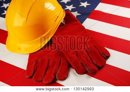 Labor day concept. Yellow helmet and gloves on USA national flag background