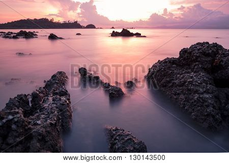 long exposure seascape with rock and sunset.