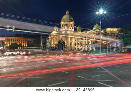 Building of National Assembly of Serbia at night with the light trails of the buses and cars passing by on busy intersection.