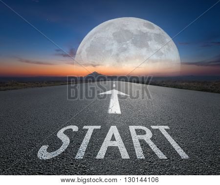 Driving on an empty imaginative road towards the big fantasy moon with sign start on asphalt as text. Concept for success and passing time.