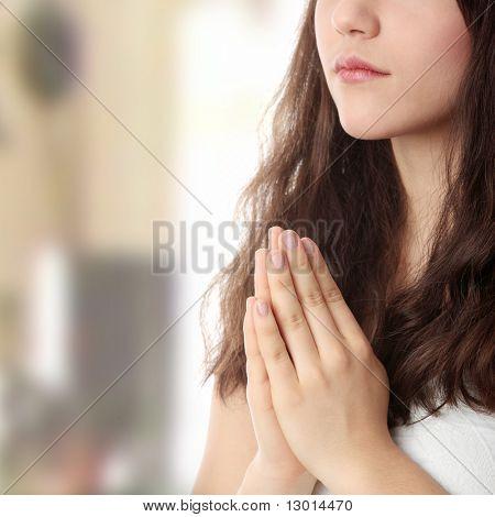 Closeup portrait of a young caucasian woman praying