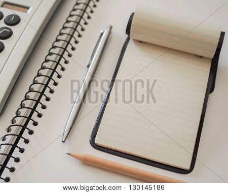 A small note pad on a larger spiral bound sketch pad with a silver cased pen a plain lead pencil and a calculator.