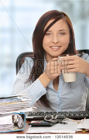 Exhausted female relaxing after filling out tax forms while sitting at her desk.