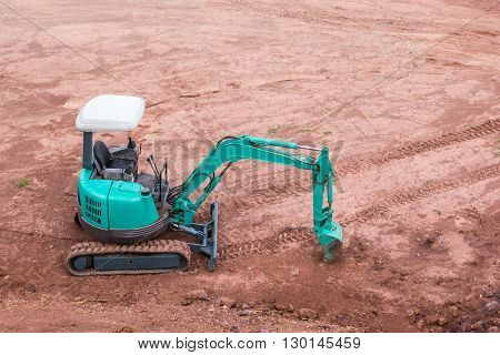 A green excavator at quarry site background.