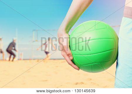 playing beach volleyball on sunny summer day