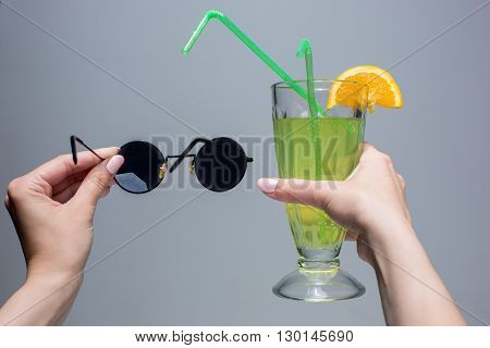 The female hands with cocktail and sunglasses on a gray background