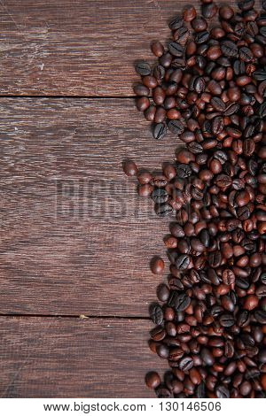 Dark roasted coffee beans on dark old wooden table texture