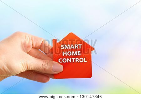 Smart home technology concept. Female hand holding model of house on bright background