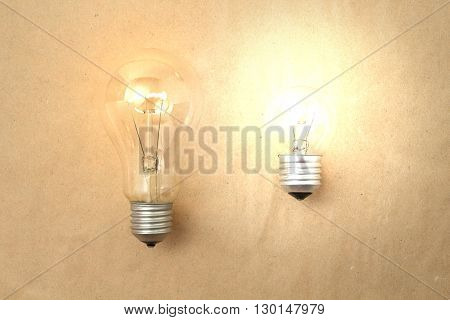 One dim light bulb and another bright light bulb on light paper background