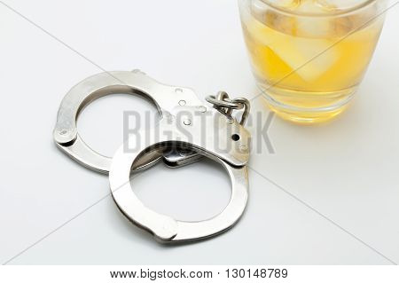Glass of whiskey and handcuffs - Drinking law concept.