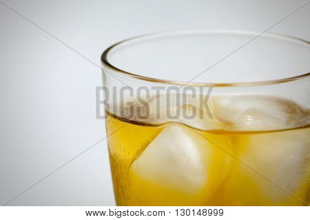 Glass of whiskey with ice in white background. (Close-up)