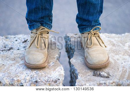 legs in leather boots on concrete wall with huge crack between