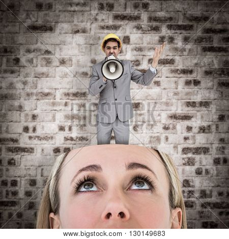 Architect with hard hat shouting with a megaphone against stone wall