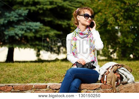 Fair-haired girl with sunglasses is sitting and keeping camera at her lap and talking by phone