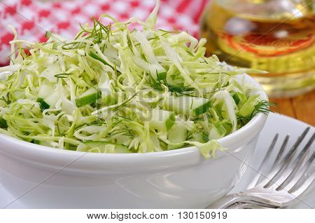 Salad of fresh coleslaw with cucumber and dill