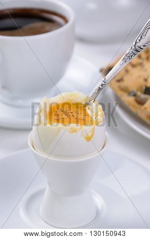 Soft-boiled egg with cup of coffee and crackers for breakfast