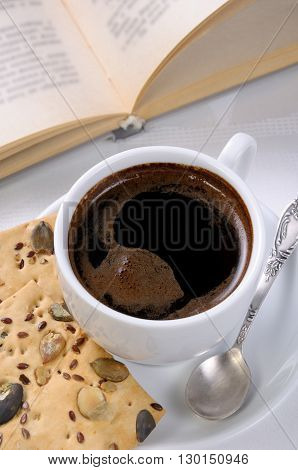 Cup of coffee and crackers on a table with an open book