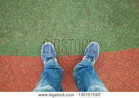 Male Feet In Jeans And Sneakers On A Stadium