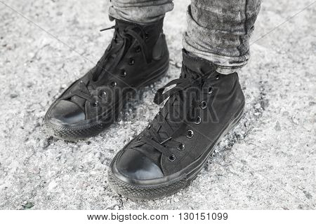 Feet In Black Gumshoes Stand On Gray Ground