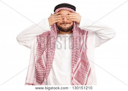 Studio shot of a young Arabian man covering his eyes isolated on white background