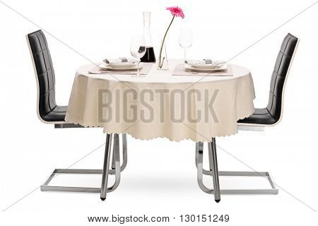 Restaurant table with two plates and a bottle of red wine isolated on white background