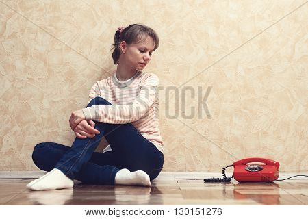 Sad girl sitting on the floor next to the red phone