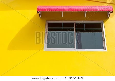 Window on yellow wall with red splash board