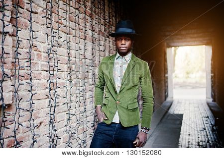 Fashion Portrait Of Black African American Man On Green Velvet Jacket, Black Hat Posed At Arch Tunne