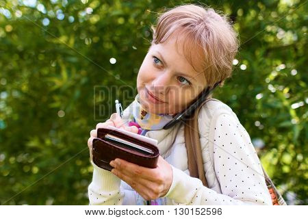 Young girl is talking by phone on the street on background of green foliage in summer phone is pressed between her ear and shoulder and girl is writing some information by pencil at sheet of paper