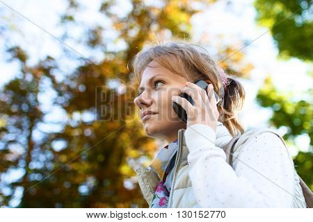 Girl is talking by phone at the background of tree foliage in sunny summer day