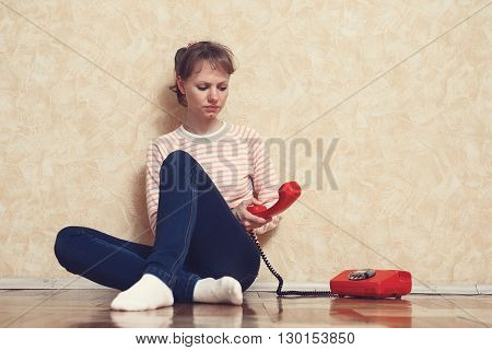 Sad young white-skinned girl is sitting on parquet floor beside the wall and calling by red phone