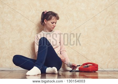 Sad young white-skinned girl is sitting on parquet floor beside the wall near to red phone