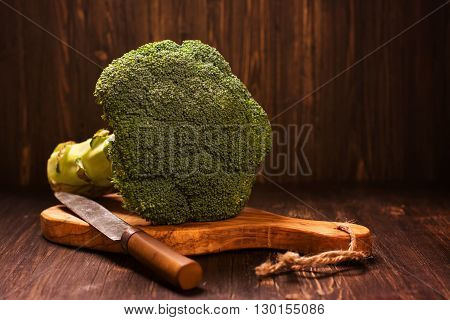Fresh whole raw broccoli cabbage with vintage knife over grunge wooden table