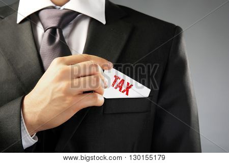 Tax Concept. Handsome businessman holding business card close up